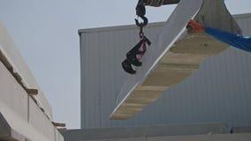 Γερανός που ανυψώνει ένα μέρος ενός συμπαγούς τοίχου σε ένα εργοτάξιο οικοδομής απόθεμα βίντεο