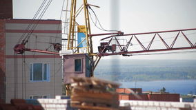 Γερανός που λειτουργεί στο εργοτάξιο οικοδομής κατοικία περιοχών σπιτιών κατοικιών οικοδόμησης κτηρίου φιλμ μικρού μήκους