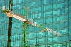 γερανός πύργων στο υπόβαθρο ενός σύγχρονου κτηρίου στοκ εικόνα