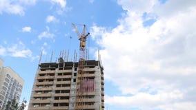 Γερανός στο εργοτάξιο οικοδομής με το ψηλό κατοικημένο κτήριο στο καλοκαίρι φιλμ μικρού μήκους