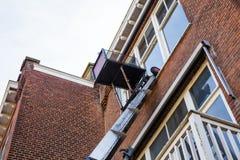 Γερανών βραχιόνων ανελκυστήρων αυτοκινήτων παραθύρων σπιτιών μπλε μπαλκόνι βοήθειας επισκευής αλλαγής πλυσίματος τούβλου υψηλό επ στοκ εικόνα με δικαίωμα ελεύθερης χρήσης