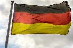 Γερμανική σημαία ενάντια στο νεφελώδη ουρανό ως μεταφορά για τους θυελλώδεις χρόνους στοκ εικόνες με δικαίωμα ελεύθερης χρήσης