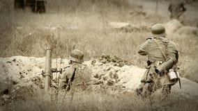 Γερμανικοί στρατιώτες που πυροβολούν με ένα τουφέκι και ένα κονίαμα στην τάφρο. WWII παλαιός κινηματογράφος ταινιών φιλμ μικρού μήκους