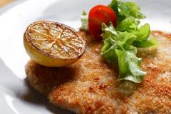 Γερμανικό schnitzel με τα λεμόνια και τους ασβέστες, ντομάτες και σαλάτα μαρουλιού αρνιών ` s Στοκ φωτογραφίες με δικαίωμα ελεύθερης χρήσης