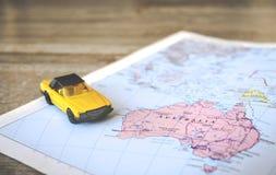 Γεωγραφικός χάρτης της Αυστραλίας με το κίτρινο μετατρέψιμο αυτοκίνητο Στοκ Φωτογραφίες