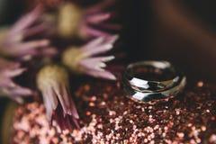 Γεωμετρικά αρχικά γαμήλια δαχτυλίδια του χρυσού στα λαμπρά λαμπιρίζοντας ρόδινα παπούτσια εκτός από τα λουλούδια Κινηματογράφηση  στοκ εικόνες
