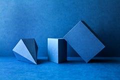 Γεωμετρική σύνθεση ζωής αριθμών ακόμα Τρισδιάστατα tetrahedron πυραμίδων πρισμάτων ορθογώνια αντικείμενα κύβων στο μπλε Στοκ Φωτογραφίες