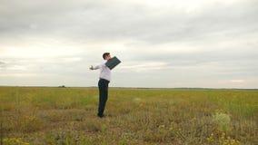 Γεωπόνος στο άσπρο πουκάμισο και δεσμός με το χαρτοφύλακα στο χέρι του whirlwind κατά την πτήση στο κλίμα των σκοτεινών σύννεφων  φιλμ μικρού μήκους