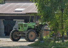 Γεωργικό αγρόκτημα και το παλαιό πράσινο τρακτέρ Στοκ εικόνα με δικαίωμα ελεύθερης χρήσης