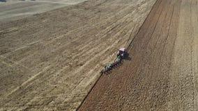 Γεωργικό τρακτέρ με το άροτρο που οργώνει τον τομέα πρίν φυτεύει την εναέρια άποψη απόθεμα βίντεο