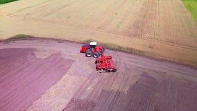 Γεωργικό τρακτέρ με το ρυμουλκό που οργώνει στο γεωργικό τομέα απόθεμα βίντεο