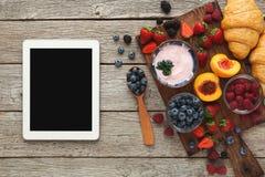 Γεύματα και smartphone πρωινού στον αγροτικό ξύλινο πίνακα στοκ φωτογραφία