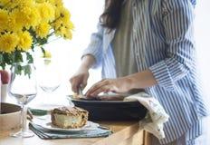 Γεύμα για την οικογένεια γυναίκα που δίνει τις μερίδες των τροφίμων εξυπηρετούμενος πίνακας κίτρινα λουλούδια στον πίνακα πίνακας στοκ εικόνα με δικαίωμα ελεύθερης χρήσης