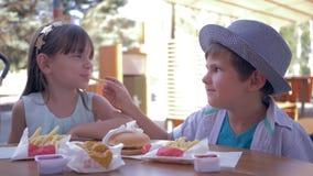 Γεύμα παλιοπραγμάτων για τα παιδιά, φροντίζοντας χαριτωμένη ταΐζοντας φίλη αγοριών με τις τηγανιτές πατάτες κατά τη διάρκεια του  απόθεμα βίντεο