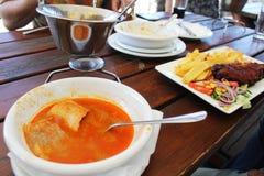 Γεύμα στο εστιατόριο - η ουγγρική σούπα ψαριών ονόμασε halaszle και τηγάνισε τους μπακαλιάρους με τις τηγανιτές πατάτες και τα λα στοκ εικόνες