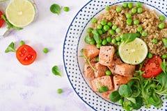 γεύμα υγιές Φέτες του ψημένου στη σχάρα σολομού, quinoa, των πράσινων μπιζελιών, των φύλλων ντοματών, ασβέστη και μαρουλιού στοκ εικόνες