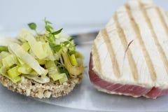 Γεύμα - ψημένη στη σχάρα μπριζόλα τόνου με τους πόρους κρεμμυδιών anmd Στοκ Εικόνες