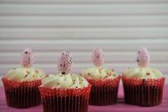 Γεύση χρονικής σοκολάτας Πάσχας cupcakes που ολοκληρώνεται με τις ρόδινες διακοσμήσεις αυγών σε έναν ξύλινο ρόδινο πίνακα Στοκ φωτογραφία με δικαίωμα ελεύθερης χρήσης