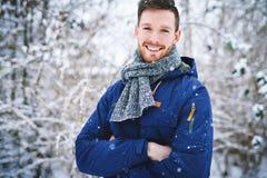 Γελώντας άτομο στο παλτό στο χιονώδες υπόβαθρο Στοκ Φωτογραφία