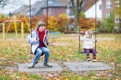Γελώντας αγόρι και η αδελφή μικρών παιδιών του σε μια ταλάντευση στοκ εικόνα