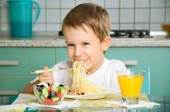 Γελώντας αγόρι που τρώει τα μακαρόνια και το κράτημα του δικράνου Στοκ φωτογραφίες με δικαίωμα ελεύθερης χρήσης
