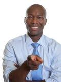 Γελώντας αφρικανικός επιχειρηματίας με το δεσμό που δείχνει   Στοκ φωτογραφία με δικαίωμα ελεύθερης χρήσης