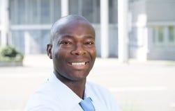 Γελώντας αφρικανικός επιχειρηματίας μπροστά από το γραφείο του Στοκ Εικόνα