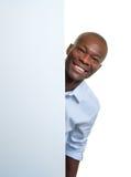 Γελώντας αφρικανικός επιχειρηματίας πίσω από μια πινακίδα Στοκ Εικόνες