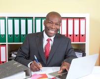 Γελώντας αφρικανικός επιχειρηματίας που γράφει ένα μήνυμα Στοκ Εικόνες