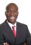 Γελώντας αφρικανικός επιχειρηματίας σε ένα μαύρο κοστούμι Στοκ Εικόνα