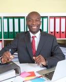 Γελώντας αφρικανικός επιχειρηματίας στο γραφείο του Στοκ φωτογραφία με δικαίωμα ελεύθερης χρήσης
