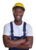 Γελώντας αφρικανικός εργάτης οικοδομών με τα διασχισμένα όπλα Στοκ Φωτογραφίες