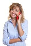 Γελώντας γυναίκα με τα σγουρά ξανθά μαλλιά στο τηλέφωνο Στοκ εικόνα με δικαίωμα ελεύθερης χρήσης