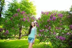 Γελώντας γυναίκα με τη μακριά υγιή τρίχα στο πάρκο σε ένα ιώδες υπόβαθρο στοκ φωτογραφίες με δικαίωμα ελεύθερης χρήσης