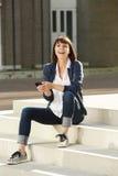 Γελώντας γυναίκα με το έξυπνο τηλέφωνο στα βήματα Στοκ φωτογραφία με δικαίωμα ελεύθερης χρήσης