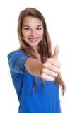 Γελώντας γυναίκα σε ένα μπλε πουκάμισο που παρουσιάζει αντίχειρα στοκ φωτογραφίες