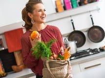 Γελώντας γυναίκα στο σχεδιάγραμμα, φρούτα και λαχανικά πτώσης στην κουζίνα Στοκ Εικόνες