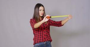 Γελώντας γυναίκα DIY που κρατά ψηλά ένα μέτρο ταινιών απόθεμα βίντεο