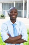 Γελώντας επιχειρηματίας από την Αφρική με τα διασχισμένα όπλα Στοκ Εικόνες