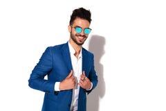 Γελώντας κομψός νεαρός άνδρας στα γυαλιά ηλίου που κρατά το περιλαίμιό του στοκ φωτογραφία με δικαίωμα ελεύθερης χρήσης