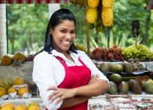 Γελώντας μεξικάνικη πωλήτρια με τα τροπικά φρούτα στην αγορά αγροτών Στοκ Εικόνες