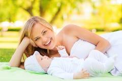 Γελώντας μητέρα που εναπόκειται σε λίγο μωρό στο κάλυμμα Στοκ φωτογραφία με δικαίωμα ελεύθερης χρήσης