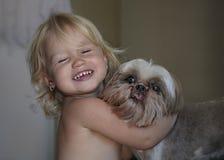 Γελώντας μικρό κορίτσι που αγκαλιάζει το σκυλί της στοκ φωτογραφίες με δικαίωμα ελεύθερης χρήσης