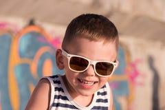 Γελώντας μικρό παιδί που φορά τα γυαλιά ηλίου και τη φανέλλα ναυτικών στο υπόβαθρο γκράφιτι Στοκ φωτογραφία με δικαίωμα ελεύθερης χρήσης