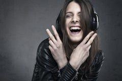 Γελώντας νέα γυναίκα με τα επικεφαλής τηλέφωνα που ακούει τη μουσική ενάντια Στοκ εικόνα με δικαίωμα ελεύθερης χρήσης