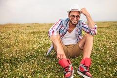 Γελώντας νεαρός άνδρας που κρατά το χέρι του στο καπέλο Στοκ φωτογραφία με δικαίωμα ελεύθερης χρήσης