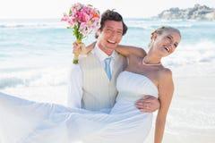 Γελώντας νεόνυμφος που φέρνει την αρκετά ξανθή σύζυγό του που χαμογελά στη κάμερα Στοκ Εικόνα