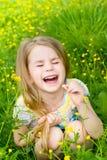 Γελώντας ξανθό μικρό κορίτσι με τις ιδιαίτερες προσοχές που κάθεται στη χλόη Στοκ Εικόνες