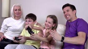 Γελώντας οικογένεια που παίζει τα τηλεοπτικά παιχνίδια σε ένα καθιστικό απόθεμα βίντεο
