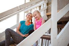 Γελώντας συνεδρίαση μητέρων και κορών στα βήματα σπιτιών παραλιών Στοκ φωτογραφία με δικαίωμα ελεύθερης χρήσης